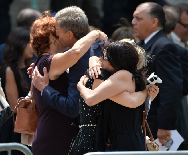 """Mourners embrace outside the Cathedral Church of St. John the Divine after the funeral service for """"Sopranos"""" actor James Gandolfini on June 27, 2013 in New York. Gandolfini, who was on a working vacation in Rome, died last week. An autopsy determined his death was the result of a heart attack. (Stan Honda/Getty Images)"""