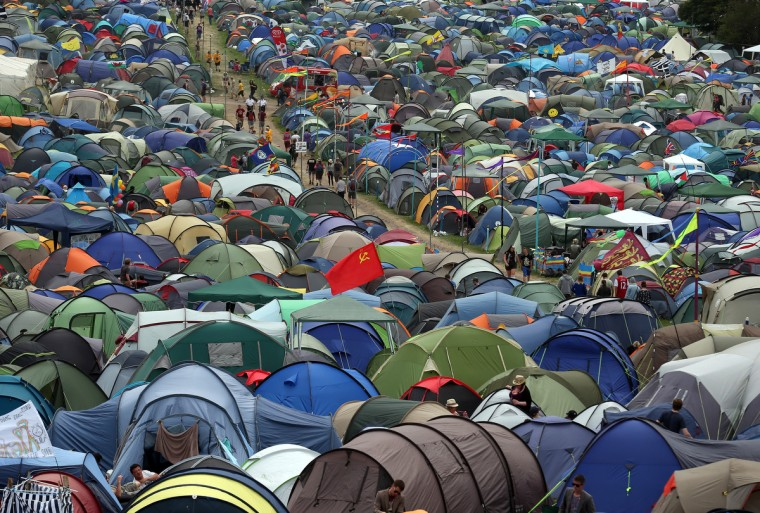 People walk past tents at the Glastonbury Festival of Contemporary Performing Arts site at Worthy Farm, Pilton on June 27, 2013 near Glastonbury, England. Gates opened on Wednesday at the Somerset Diary Farm that will be playing host to one of the largest music festivals in the world and this year features headline acts Artic Monkeys, Mumford and Sons and the Rolling Stones. Tickets to the event which is now in its 43rd year sold out in minutes and that was before any of the headline acts had been confirmed. The festival, which started in 1970 when several hundred hippies paid 1 GBP to watch Marc Bolan, now attracts more than 175,000 people over five days. (Matt Cardy/Getty Images)