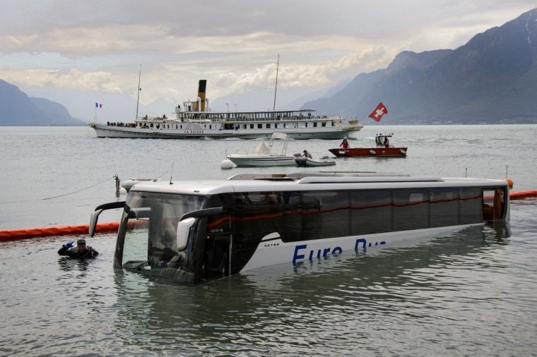 A paddle streamer of the Compagnie Generale de Navigation sur le lac Leman, commonly abbreviated to CGN, cruises on June 3, 2013 past a pullman bus during a rescue operation after it sank in Lake Geneva off the coast of Vevey, western Switzerland. The empty bus parked at the market square in Vevey rolled on its own and ended up in Lake Geneva. No one was injuried. (Fabrice Coffrini/Getty Images)