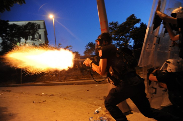 Turkish riot police officer fires tear gas during clashes with protestors between Taksim and Besiktas in Istanbul during a demonstration against the demolition of the park. Turkish police on June 1 began pulling out of Istanbul's iconic Taksim Square, after a second day of violent clashes between protesters and police over a controversial development project. Thousands of demonstrators flooded the site as police lifted the barricades around the park and began withdrawing from the square. What started as an outcry against a local development project has snowballed into widespread anger against what critics say is the government's increasingly conservative and authoritarian agenda. (Bulent Kilic/Getty Images)