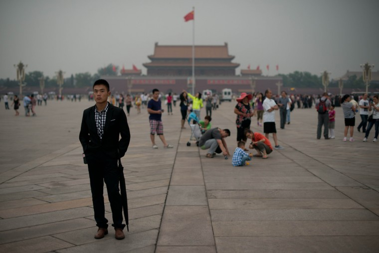 A plain-clothes policeman (L) follows suspected journalists on Tiananmen square in Beijing. Authorities launch a major push every June 4 to prevent discussion of the violently crushed 1989 pro-democracy protests, in which at least hundreds of people died. (Ed Jones/Getty Images)