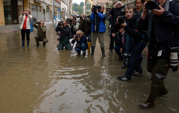Photographers and cameramen stand in a street submerging in the floods of the river Elbe in Pirna, eastern Germany, to take pictures of the German Chancellor during her visit on June 4, 2013. German Chancellor Angela Merkel pledged 100 million euros ($130 million) in emergency aid for flood-ravaged areas, as surging waters that have already claimed 10 lives and forced tens of thousands of evacuations across Europe bore down towards Germany. (Johannes Eisele/Getty Images)
