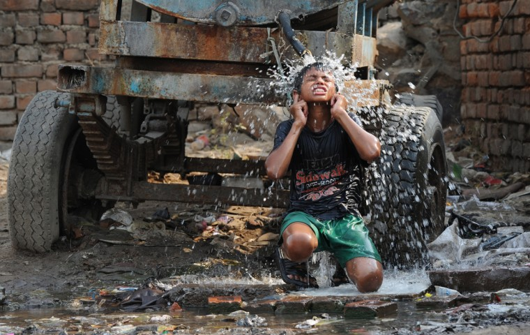 An Indian boy cools off under a water tanker in New Delhi. The weather department has forecast India will receive normal rains this year, raising prospects of a stronger performance by Asia's third-largest economy. (Sajjad Hussain/Getty Images)
