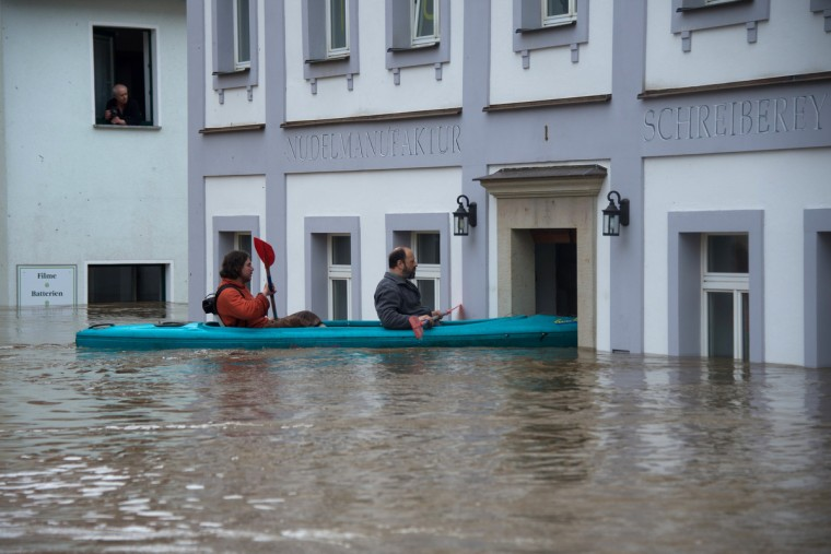 People canoe in the flooded city of Wehlen, in eastern Germany, on June 4, 2013. Torrential rain and heavy flooding hit central Europe. (Johannes Eisele/Getty Images)