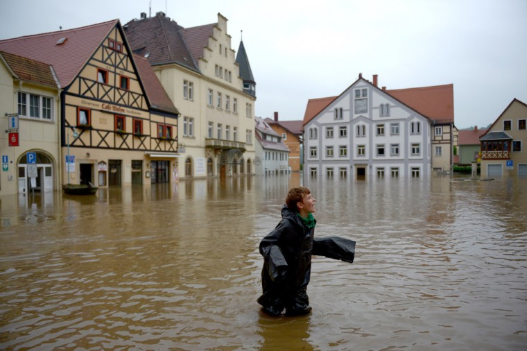A boy stands in the flooded city of Wehlen, in eastern Germany, on June 4, 2013. Torrential rain and heavy flooding hit central Europe. (Johannes Eisele/Getty Images)