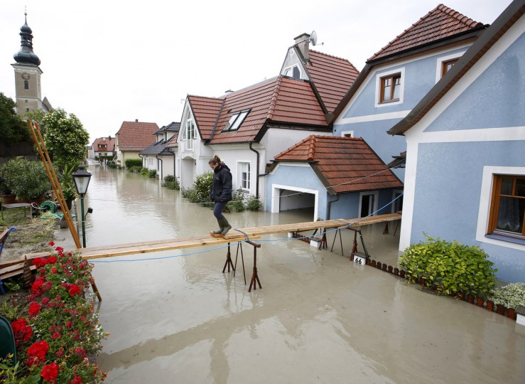 A women crosses a makeshift bridge over overflooded streets in Unterloiben, Austria on June 4, 2013. Torrential rain and heavy flooding hit central Europe. (Dieter Nagl/Getty Images)