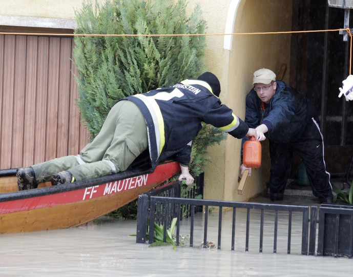 A firefighter in a boat delivers a canister with gasoline to a man in a flooded house in Unterloiben on June 4, 2013. Torrential rain and heavy flooding hit central Europe. (Dieter Nagl/Getty Images)