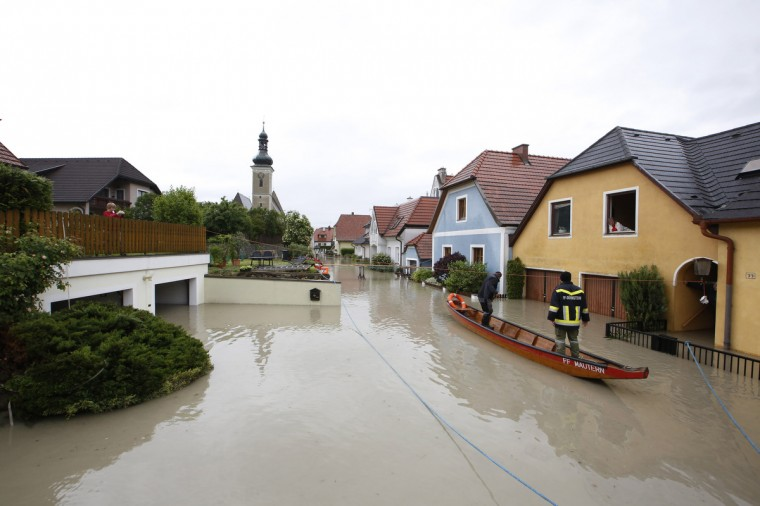 Firefighters are pictured in a boat in Unterloiben, Austria, on June 4, 2013. Torrential rain and heavy flooding hit central Europe. (Dieter Nagl/Getty Images)