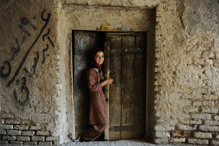 An Afghan girl stands in the doorway of her house in the old sector of Herat. Over a third of Afghans are living in abject poverty, as those in power are more concerned about addressing their vested interests rather than the basic needs of the population, a UN report said. (Aref Karimi/Getty Images)