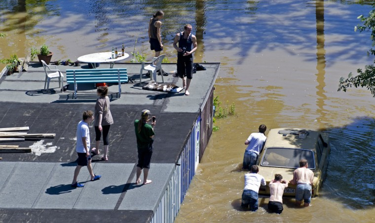 Residents push a car out of a garage flooded by the river Elbe in Dresden, eastern Germany, on June 5, 2013. German Chancellor Angela Merkel pledged 100 million euros in emergency aid for flood-ravaged areas as surging waters that have claimed at least 11 lives and forced tens of thousands of evacuations across central Europe bore down on eastern Germany. (Robert Michael/Getty Images)