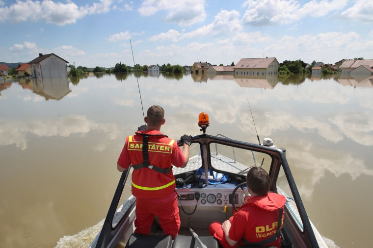 Members of the German Life Saving Association DLRG, patrol onboard a boat through the flooded streets in Deggendorf, Bavaria, 5 June 2013, after the Danube river broke its banks. Cities in Germany and the Czech Republic were scrambling to stave off potential disaster as a flood wave headed north, sending thousands of people fleeing their homes. (Karl-Josef Hildenbrand/Getty Images)