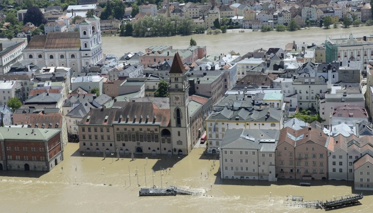 Houses are flooded by the river Danube (front) and Inn (back) in Passau, southern Germany, on June 5, 2013. German Chancellor Angela Merkel pledged 100 million euros in emergency aid for flood-ravaged areas as surging waters that have claimed at least 11 lives and forced tens of thousands of evacuations across central Europe bore down on eastern Germany. (Christof Stache/Getty Images)
