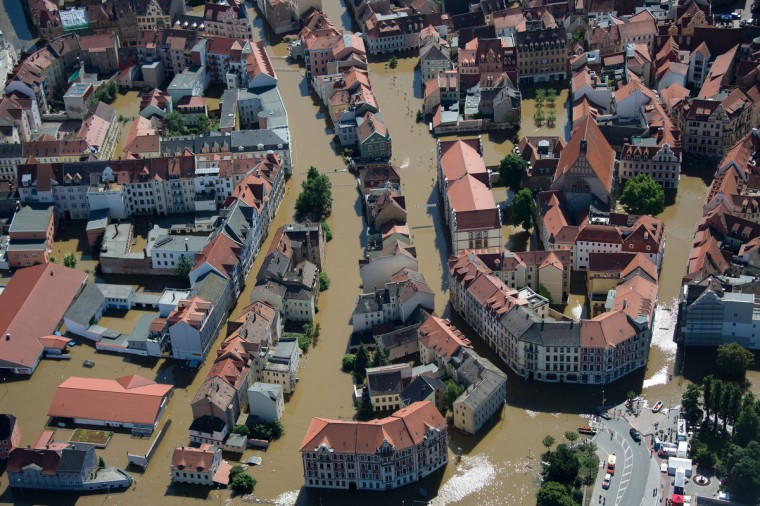 Aerial view shows a boat with rescue personal making their way through the flooded city of Meissen, eastern Germany, on June 5, 2013. German, Czech and Austrian river cities braced for rising flood waters, evacuating thousands and boosting defences along the swollen Elbe and Danube, after inundations from heavy rains left 11 people dead. (Johannes Eisele/Getty Images)