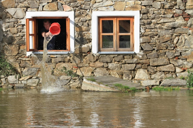 A man pours water out of the window of a house in the river Blanice in Putim, near Pisek, Czech Republic. German, Czech and Austrian river cities braced for rising flood waters, evacuating thousands and boosting defences along the swollen Elbe and Danube, after inundations from heavy rains left 11 people dead. (Radek Mica/Getty Images)