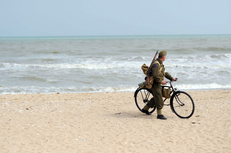 A man dressed as a World War II soldier walks with a bicycle along Juno Beach in Courseulles-sur-Mer during the commemoration of the 69th anniversary of the D-Day landing in Normandy. As part of D-Day commemorations, a ceremony was held in Courseulles-sur-Mer to mark the 10 year anniversary of the June Beach centre in Courseulles-sur-Mer, Canada's Second World War museum in Normandy. On June 6 1944, American, British, and Canadian troops launched an assault on Nazi German forces which were occupying the northern French coast, in a battle which marked the beginning of the liberation of France and the victory of allied forces over Nazi Germany in the Second World War. (Thomas Bregardis/Getty Images)