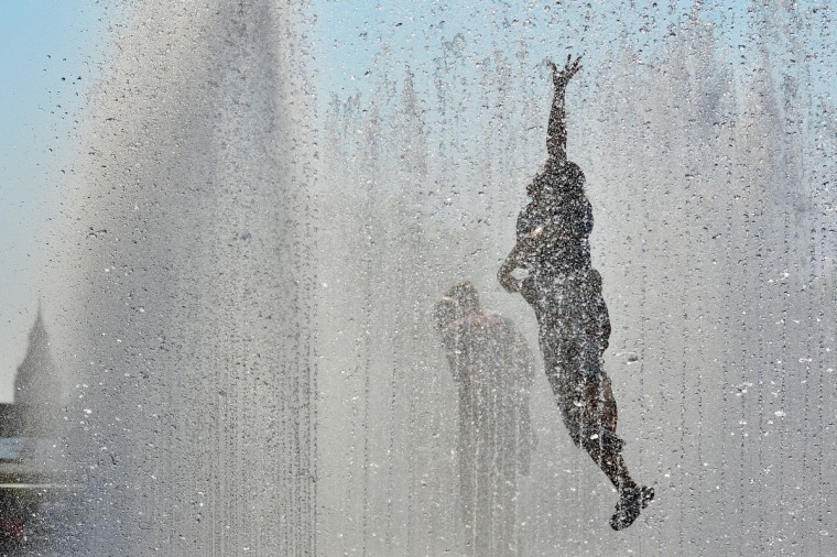 A woman enjoys a water fountain in London's Southbank as Britain finally enjoys warm June weather following one of the coldest winters and Springs in years. (Ben Stansall/Getty images)