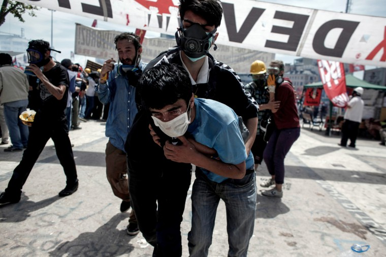 "A demonstrator helps another protester during clashes with riot police in Istanbul's Taksim square. Turkish Prime Minister Recep Tayyip Erdogan on June 11 said he had ""no more tolerance"" for the mass anti-government demonstrations that have engulfed the country, as police clashed with demonstrators in Istanbul on a 12th day of unrest. (Angelos Tzortzinis/Getty Images)"