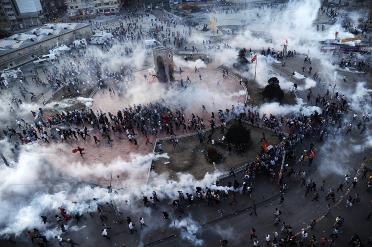"People run away as Turkish riot policemen fire tear gas on Taksim square. Turkish police fired massive volleys of tear gas and jets of water to disperse thousands of anti-government demonstrators in Istanbul's Taksim Square on June 11, after earlier apparently retreating, an AFP reporter saw. The gas sent the crowd scrambling, raising tensions on a 12th day of violence after Prime Minister Recep Tayyip Erdogan warned he had ""no more tolerance"" for the mass demonstrations. (Bulent Kilic/Getty Images)"