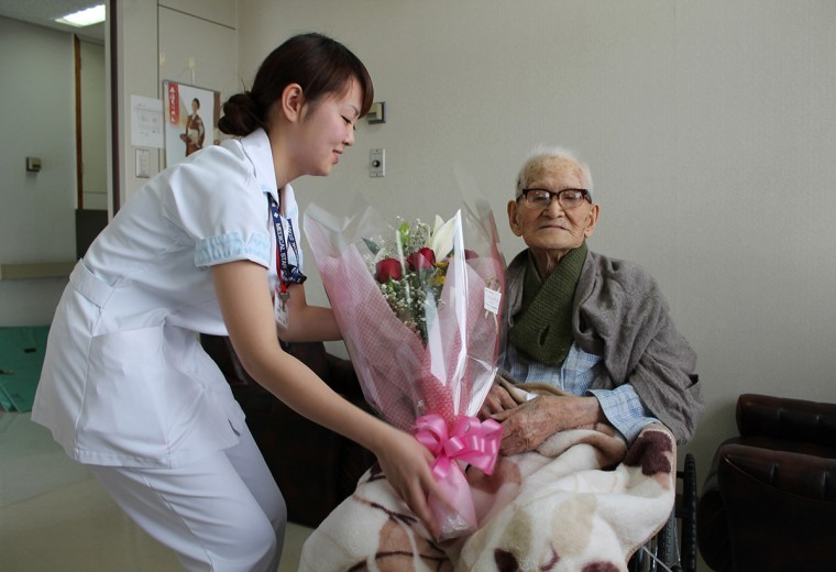 This picture taken by the Kyotango City Government on December 26, 2012 shows the world's oldest man Jiroemon Kimura (R) receiving a flower bouquet from a nurse at a hospital in Kyotango, Kyoto prefecture in western Japan. The world's oldest person and the oldest man Kimura died of natural causes in a hospital in Kyotango on June 12, 2013 at the age of 116. (AFP/Getty Images)