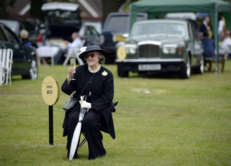 A race goer raises a glass of champagne while she waits for friends during the first day of Royal Ascot, in Berkshire, west of London. (Adrian Dennis/Getty Images)