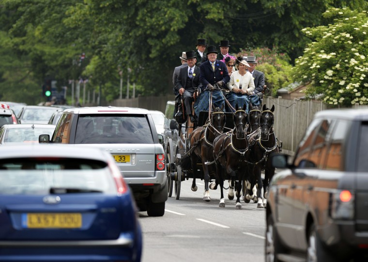 Racegoers are driven on a horse drawn carriage before the second day of Royal Ascot, in Berkshire, west of London. (Adrian Dennis/Getty images)