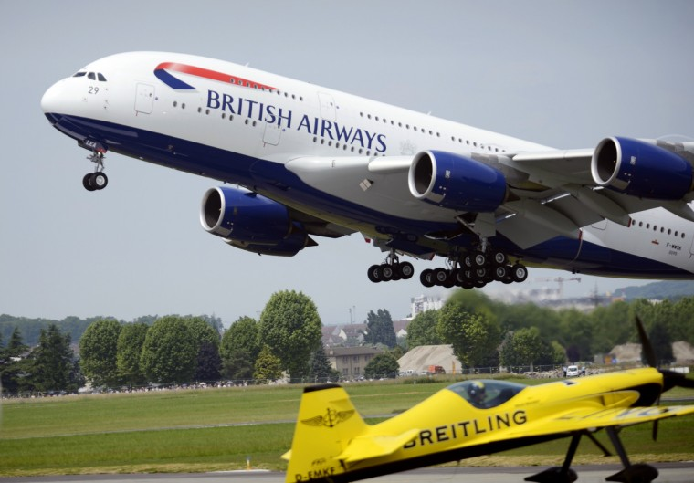 A British Airway Airbus A 380 takes off above an acrobatic plane on Le Bourget airport, near Paris on June 19, 2013 during the 50th International Paris Air show. (Eric Feferberg/Getty Images)