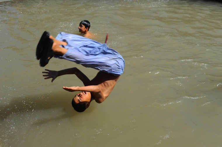 An Afghan youth dives into the Herat River in Herat. Over a third of Afghans are living in abject poverty, as those in power are more concerned about addressing their vested interests rather than the basic needs of the population, a UN report said. (Aref Karimi/Getty Images)