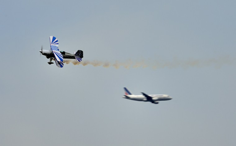 An acrobatic plane flies over a Air France flight in the background on Le Bourget airport, near Paris on June 19, 2013 during the 50th International Paris Air show. (Eric Feferberg/Getty Images)