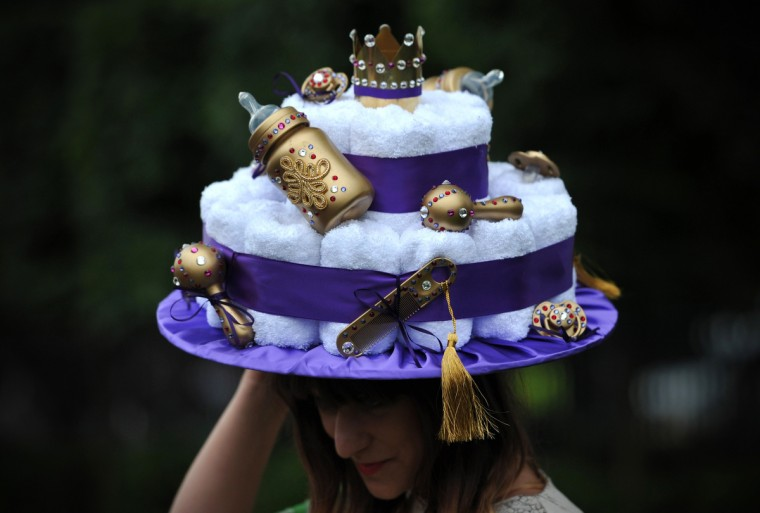A woman poses for a photograph in a royal baby-themed hat during the third day of Royal Ascot, in Berkshire, west of London. (Carl Court/Getty images)