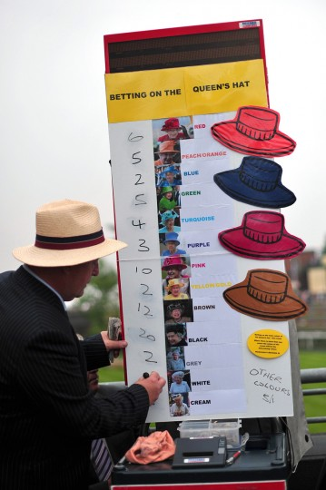 A bookmaker takes bets on the color of the hat that Queen Elizabeth II will be wearing on the third day of Royal Ascot, in Berkshire, west of London. (Carl Court/Getty images)