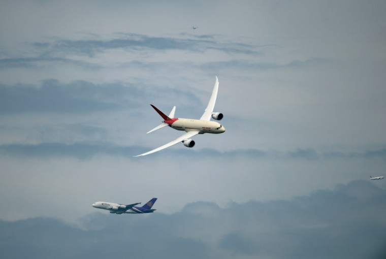 An Air India Boeing Dreamliner (C) crosses a Thai Airway Airbus A 380 (bottom in the background) flying over Le Bourget airport with two other jets, near Paris on June 20, 2013 during the 50th International Paris Air show. (Eric Feferberg/Getty Images)