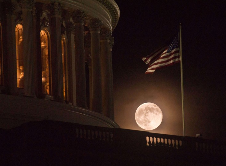 The full moon rises behind the US Capitol in Washington. (Kamm/Getty images)