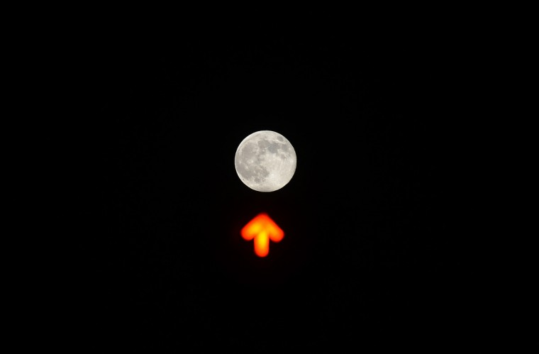 A picture shows the moon over a traffic light in downtown Rome. (Filippo Monteforte/Getty images)