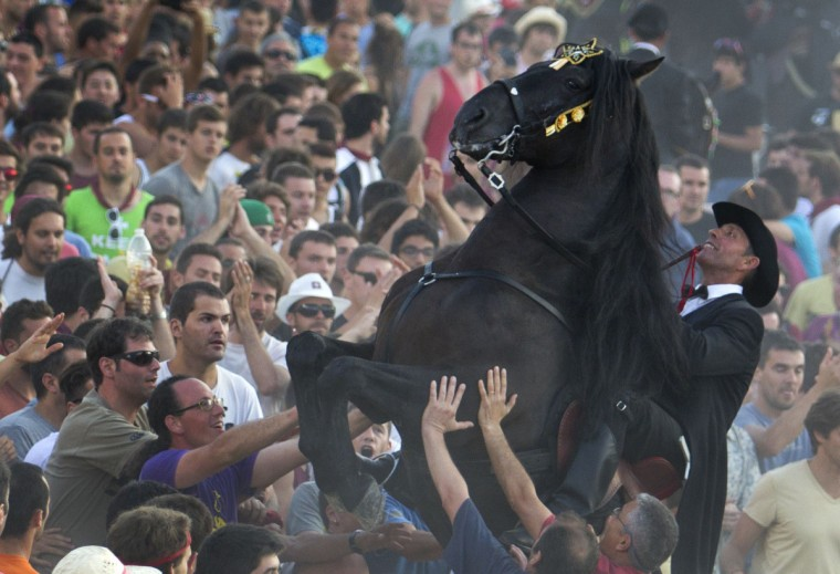 A horse rears in a crowd during the traditional San Juan's (Saint John) festival in the town of Ciutadella, on the Balearic Island of Menorca, Spain on June 24, 2013, on the eve of Saint John day. (Jaime Reina/Getty Images)