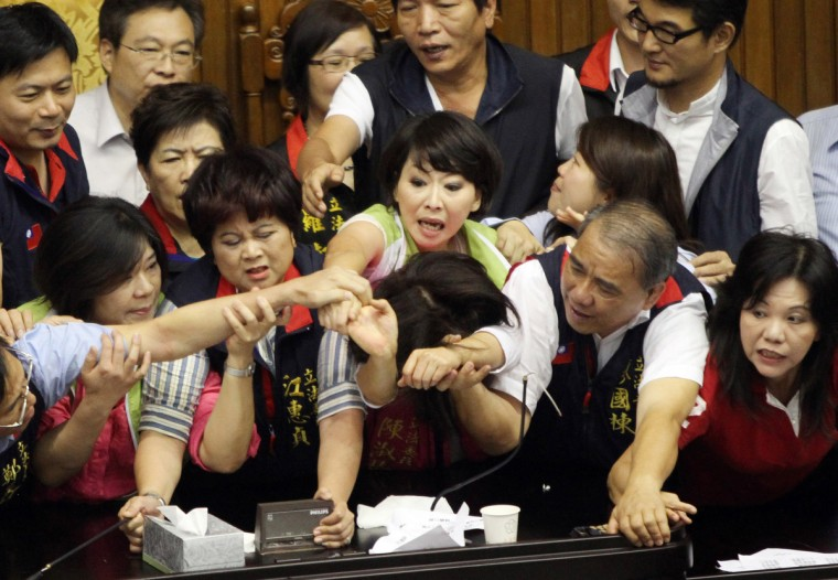 Legislators from Taiwan's ruling Kuomintang party and opposition try to seize the parliament's podium. Fighting broke out in Taiwan's parliament as legislators scuffled and threw coffee during a debate on whether a controversial capital gains tax on share trading should be revised less than a year after it was brought in. (Getty Images)
