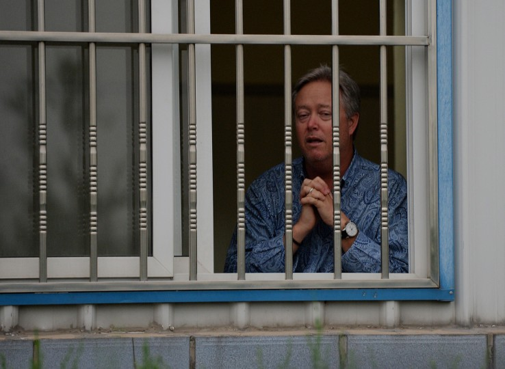 US businessman Chip Starnes stands behind the bars of his office window after being held hostage for five days over a wage dispute at his Specialty Medical Supplies factory in Huairou, Beijing. Starnes, who had come from the US-based company to lay off 30 employees, said the remaining 100 then barred him from leaving until they reached a resolution. (Mark Ralston/Getty Images)