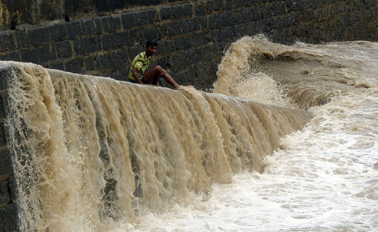 An Indian boy sits on a sea wall as waves lash the retaining wall of the iconic Gateway of India off the Arabian sea in Mumbai. The monsoon season, which runs from June to September, accounts for about 80 percent of India's annual rainfall, vital for a farm economy which lacks adequate irrigation facilities. However, the monsoon arrived early this year, catching many by surprise and exposing a lack of preparedness. (Indranil Mukherjee/Getty Images)