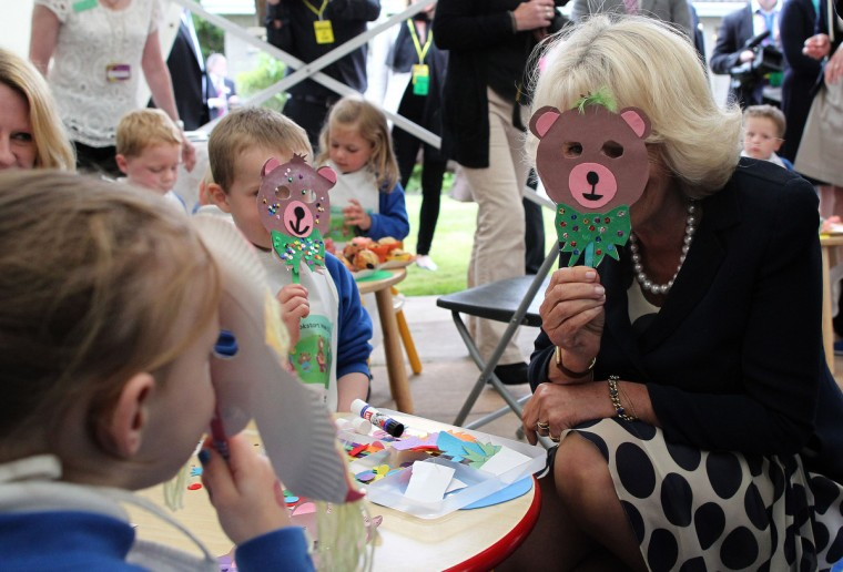 Britain's Camilla, Duchess of Cornwall holds a cut-out bear mask in front of her face as she chats with school children from Broughshane Primary School during a visit to Broughshane library in Broughshane, Northern Ireland. (Peter Muhly/Getty Images)