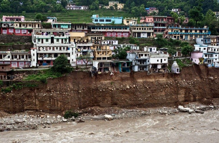 Damaged houses are seen precariously above the flash flood-eroded Mandakini river in the town of Tilwara, around 30kms from Rudraprayag. Around 1,000 people have been killed in flash floods and landslides in northern India, as a top official warned June 24 that rebuilding of the devastated Himalayan region would take years. (Manan Vatsyayana/Getty Images)
