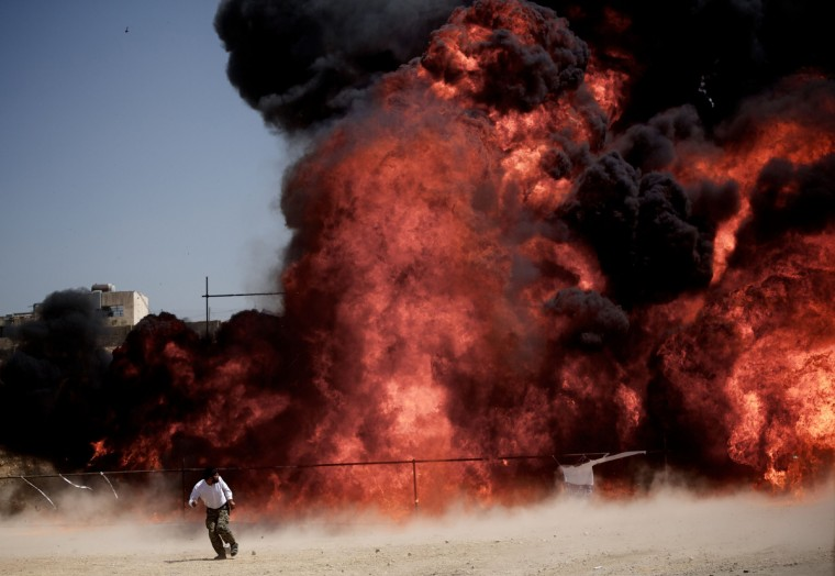 An Iranian man who was fixing explosives wires run away after setting ablaze 50 tons of drugs seized in recent months in eastern Tehran on June 26, 2013 to mark the International Day Against Drug Abuse and Illicit Trafficking. (Behrouz Mehri/Getty Images)