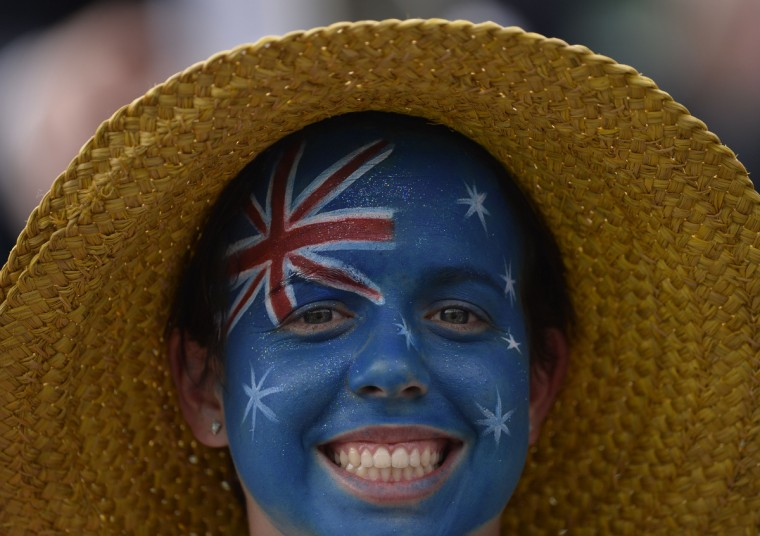An Australian fan with a painted face poses for a picture as Germany's Dustin Brown plays against Australia's Lleyton Hewitt during their second round men's singles match on day three of the 2013 Wimbledon Championships tennis tournament at the All England Club in Wimbledon, southwest London, on June 26, 2013. Brown won 6-4, 6-4, 6-7, 6-2. (Adrian Dennis/Getty Images)