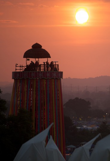 Festivalgoers look out from a viewing tower as the sun sets on the first day of the Glastonbury Festival of Contemporary Performing Arts near Glastonbury, southwest England on June 26, 2013. (Andrew Cowie/Getty Images)
