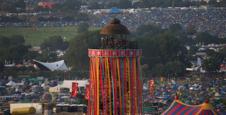 Festivalgoers look out from a viewing tower on the first day of the Glastonbury Festival of Contemporary Performing Arts near Glastonbury, southwest England on June 26, 2013. (Andrew Cowie/Getty Images)