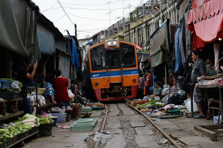 A train passes through a food market in Maeklong, some 60 kilometers south-west of Bangkok. Several times a day, shopkeepers swiftly pack up their food stalls and pull back their canopies to let the trains pass. Once the trains have rumbled through, the crates of vegetables, fish and eggs, are heaved back into their position along the tracks and shoppers return to the tracks they use as a path through the market. (Christophe Archambault/Getty images)