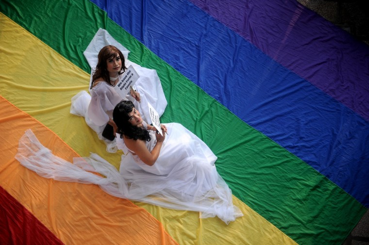 Supporters of lesbian, gay, bisexual, and transgender groups dressed in weddings gowns sit on a huge rainbow banner at the University of the Philippines (UP) campus in Manila as they celebrate Pride Month. (Noel Celis/Getty Images)