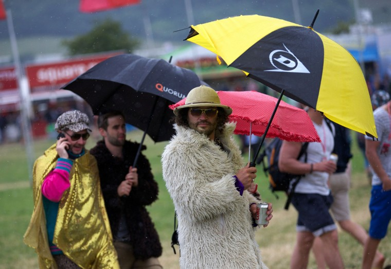 Festival goers walk around the site on the second day of the Glastonbury Festival of Contemporary Performing Arts near Glastonbury, southwest England, on June 27, 2013. (Andrew Cowie/Getty Images)