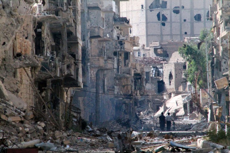 Syrians walk down a destroyed street in the centre of Syria's northeastern city of Deir Ezzor. More than 100,000 people have been killed in Syria's uprising, a watchdog said, as a proposed Geneva peace conference looked set to be delayed, dimming hopes for an end to the bloodshed. (Ahmad Aboud/Getty images)