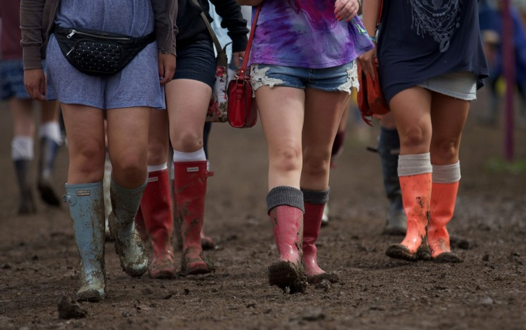 Festival goers in rubber boots walk across the site on third day of the Glastonbury Festival of Contemporary Performing Arts near Glastonbury, southwest England on June 28, 2013. (Andrew Cowie/Getty Images)