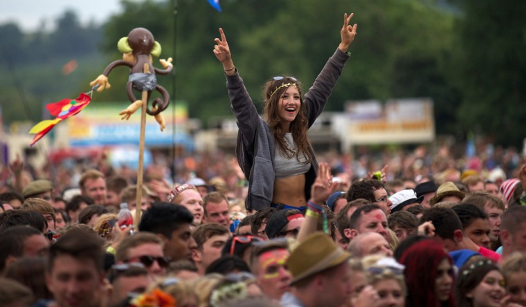 Festival goers attend concerts at the Pyramid Stage during the third day of the Glastonbury Festival of Contemporary Performing Arts near Glastonbury, southwest England, on June 28, 2013. (Andrew Cowie/Getty Images)