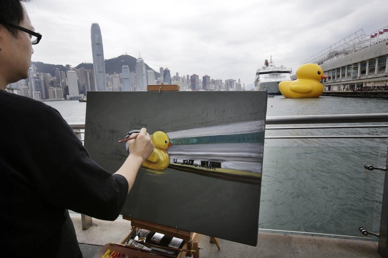 "A man paints Dutch conceptual artist, Florentijin Hofman's Floating duck sculpture called ""Spreading Joy Around the World"" as it arrives in Victoria Harbour on May 2, 2013 in Hong Kong. The ""Rubber Duck"", which is 16.5 meters high, will be in Hong Kong from May 2 to June 9. Since 2007, ""Rubber Duck"" has been traveling to 10 countries and 12 cities. (Jessica Hromas/Getty Images)"